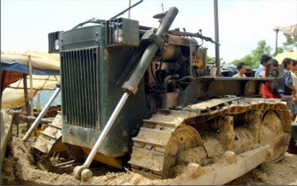 harred remains of the bulldozer after it was set on fire at a Kasom Khullen village