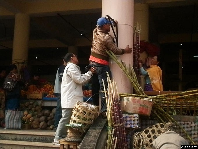James Vaiphei - fixing the flower pot frame on the pillar