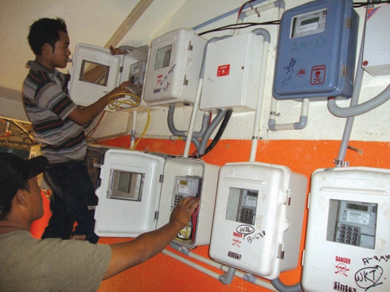 Staffs of Power Dept installing pre-paid power meters in May 2012
