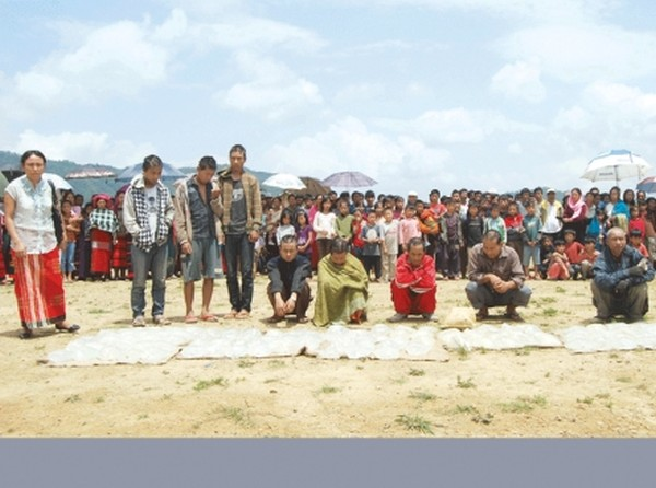 Bootleggers being penalised at Talui in Ukhrul, seized liquors being destroyed