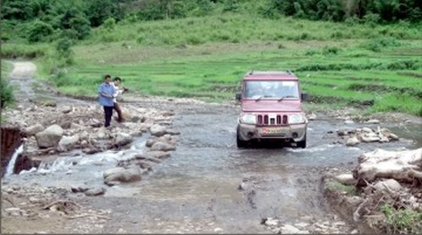 A rivulet makes its way over the middle of a road in IT Road