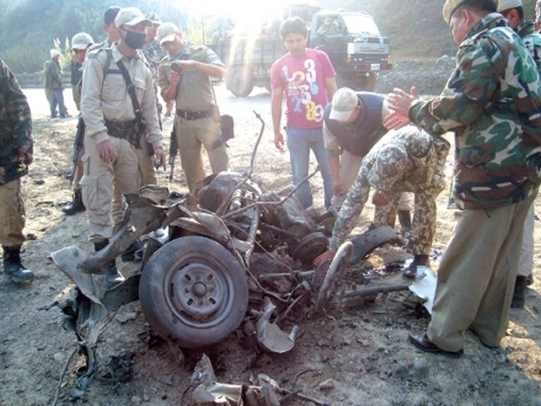 Security personnel inspecting the remnants of the IED-fitted Maruti Van at the blast site