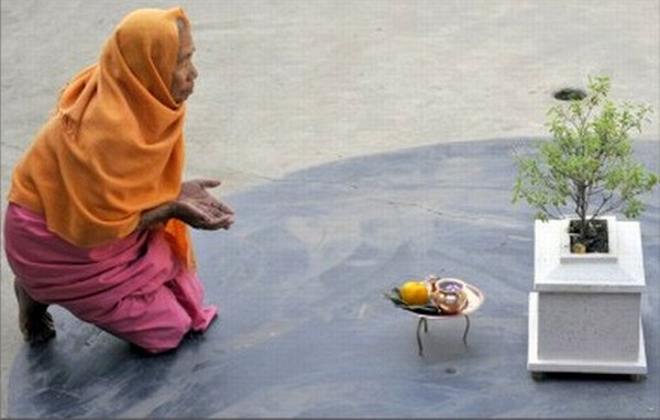 An old Manipuri woman praying in front of Tulsi